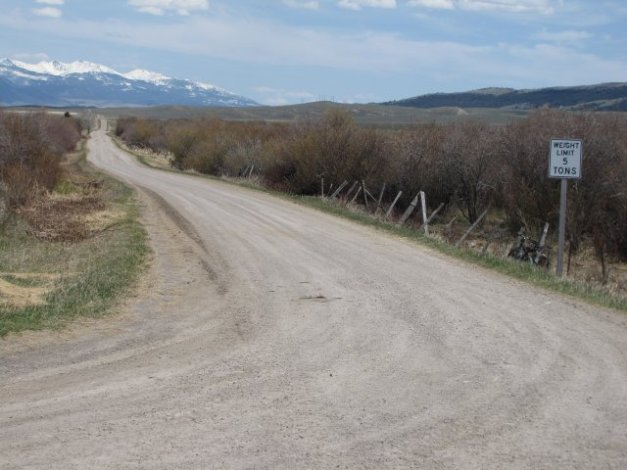 Crazy Mountains and dirt road with bridge up ahead over Flathead Creek